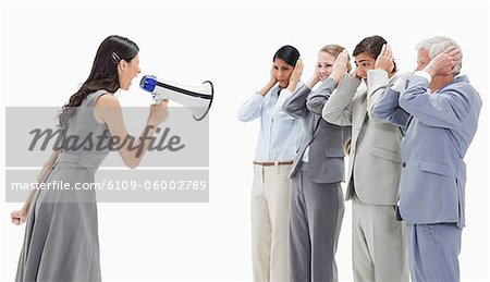 Woman yelling in a megaphone at business people against white background Stock Photo - Premium Royalty-Free, Image code: 6109-06002789