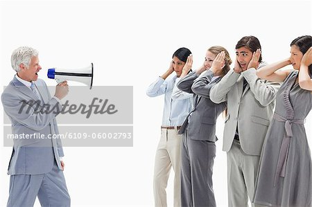 Man yelling in a megaphone at business people with their hands over their ears against white background Stock Photo - Premium Royalty-Free, Image code: 6109-06002793