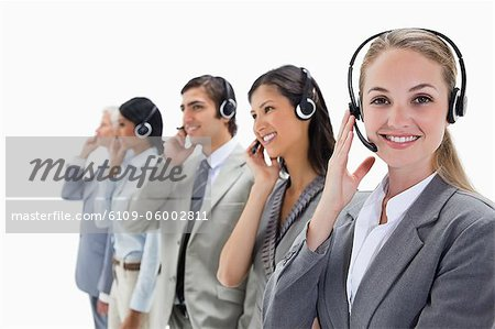 Smiling professionals listening with headsets against white background Stock Photo - Premium Royalty-Free, Image code: 6109-06002811