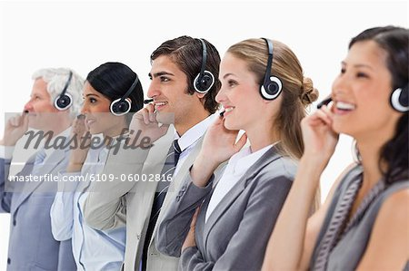 Professionals listening happily with headsets against white background Stock Photo - Premium Royalty-Free, Image code: 6109-06002816