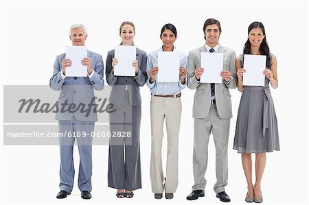 Business team holding five white placards against white background Stock Photo - Premium Royalty-Free, Image code: 6109-06002828