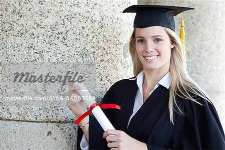 Happy graduating student wearing a gown while proudly holding her diploma Stock Photo - Premium Royalty-Free, Image code: 6109-06003569