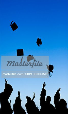 Students celebrating their graduation while throwing their hats Stock Photo - Premium Royalty-Free, Image code: 6109-06003587
