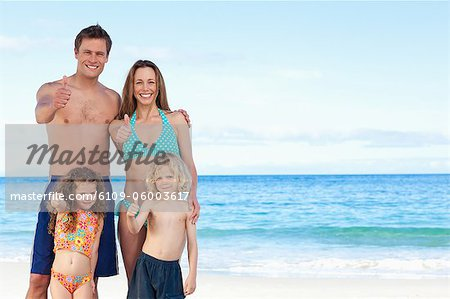 Happy young family on the beach giving thumb up Stock Photo - Premium Royalty-Free, Image code: 6109-06003617