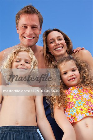 Smiling young family spending their time on the beach Stock Photo - Premium Royalty-Free, Image code: 6109-06003630