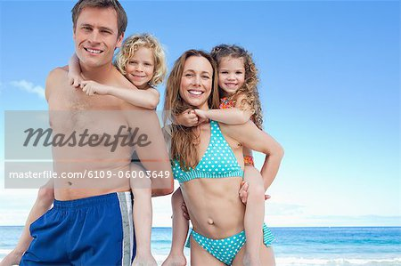 Happy young family having a nice day on the beach together Stock Photo - Premium Royalty-Free, Image code: 6109-06003649