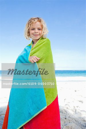 Smiling little boy on the beach wrapped into his towel Stock Photo - Premium Royalty-Free, Image code: 6109-06003710