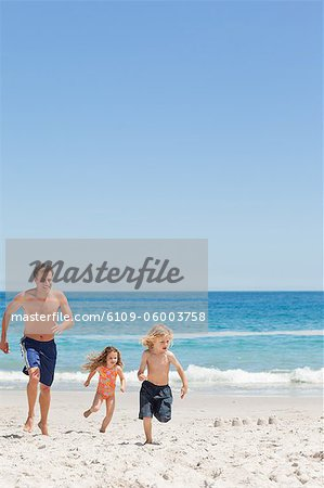 Young father running with his little children on the beach Stock Photo - Premium Royalty-Free, Image code: 6109-06003758