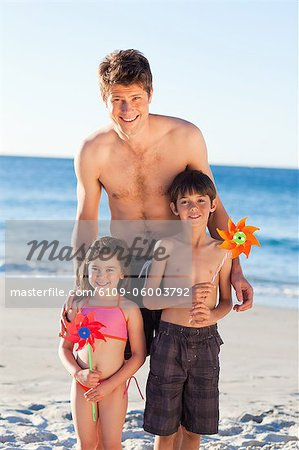 Smiling father on the beach together with his little children Stock Photo - Premium Royalty-Free, Image code: 6109-06003792