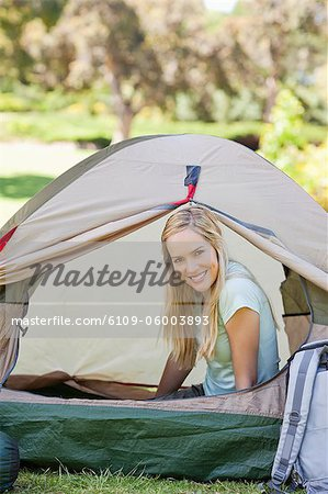 A woman almost fully inside a tent as she smiles with her head just outside the door of it Stock Photo - Premium Royalty-Free, Image code: 6109-06003893