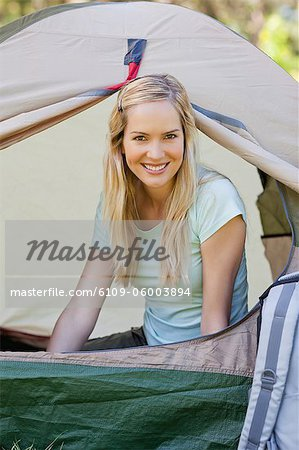 A woman smiling and sitting almost fully inside of the tent Stock Photo - Premium Royalty-Free, Image code: 6109-06003894
