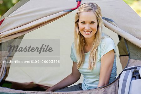 A woman inside of the tent while she looks straight ahead at the camera Stock Photo - Premium Royalty-Free, Image code: 6109-06003896