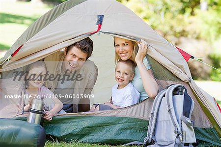While camping the entire family smiles while sitting inside the tent Stock Photo - Premium Royalty-Free, Image code: 6109-06003909