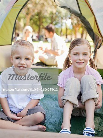 A smiling brother and sister sit inside of the tent as their parents sit outside talking Stock Photo - Premium Royalty-Free, Image code: 6109-06003911
