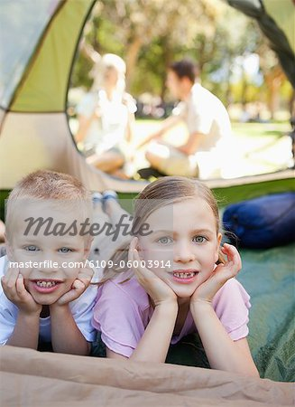 Two smiling children lie down in the tent together with their parents outside Stock Photo - Premium Royalty-Free, Image code: 6109-06003914