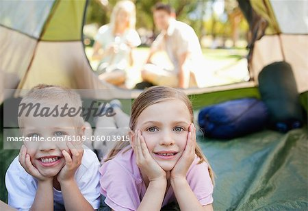 A smiling bother and sister lie down inside of the tent while their parents sit outside looking in Stock Photo - Premium Royalty-Free, Image code: 6109-06003915
