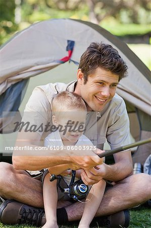 A close up shot of a dad and his boy fishing by the tent Stock Photo - Premium Royalty-Free, Image code: 6109-06003923