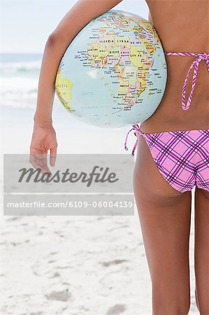 Rear view of a young woman holding a globe beach ball while standing on the beach Stock Photo - Premium Royalty-Free, Image code: 6109-06004139
