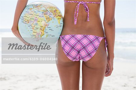 Young woman holding a globe beach ball while standing in front of the ocean Stock Photo - Premium Royalty-Free, Image code: 6109-06004140