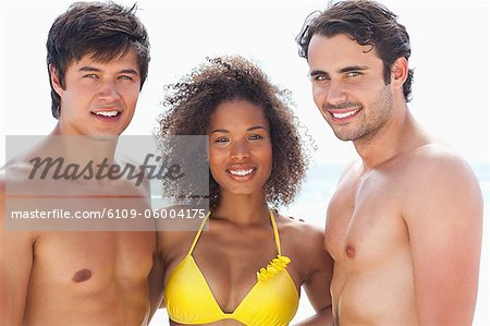 Two men and a woman wearing swimsuits while smiling as they embrace each other Stock Photo - Premium Royalty-Free, Image code: 6109-06004175