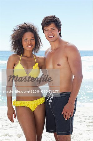 A man and a woman wearing swimsuits while smiling as they hold each other on the beach Stock Photo - Premium Royalty-Free, Image code: 6109-06004177