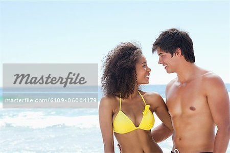 A man and a woman wearing swimsuits smiling as they put an arm around each other on the beach Stock Photo - Premium Royalty-Free, Image code: 6109-06004179