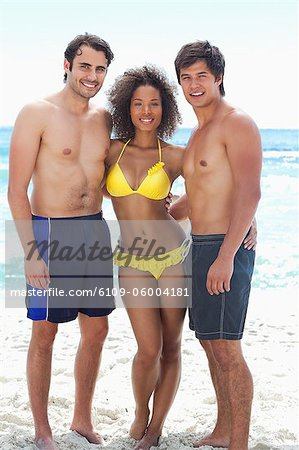 Woman wearing a yellow bikini while smiling with her arms around two men as they stand on a beach Stock Photo - Premium Royalty-Free, Image code: 6109-06004181