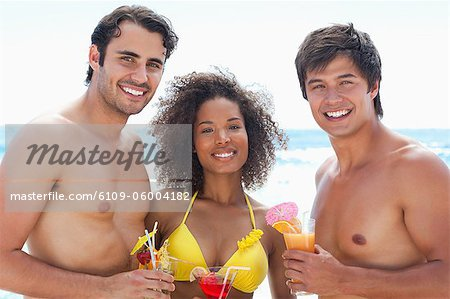 Two men and a woman wearing swimsuits while smiling as they hold cocktails on a beach Stock Photo - Premium Royalty-Free, Image code: 6109-06004182