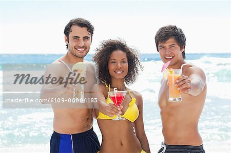 Two men and a woman in swimsuits smiling as they offer cocktails on a beach Stock Photo - Premium Royalty-Free, Image code: 6109-06004183