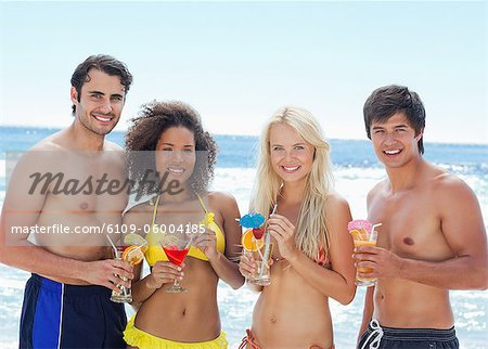 Two men and two women wearing swimsuits as they hold cocktails while standing on a beach Stock Photo - Premium Royalty-Free, Image code: 6109-06004185