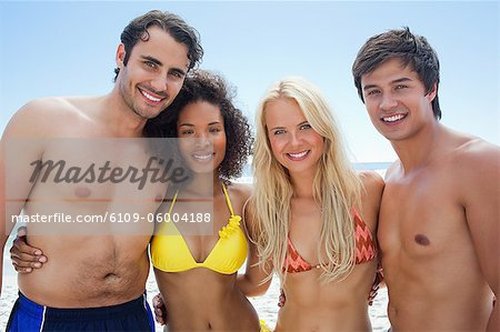 Two men and two women in swimwear smiling as they embrace each other with the sky in the background Stock Photo - Premium Royalty-Free, Image code: 6109-06004188