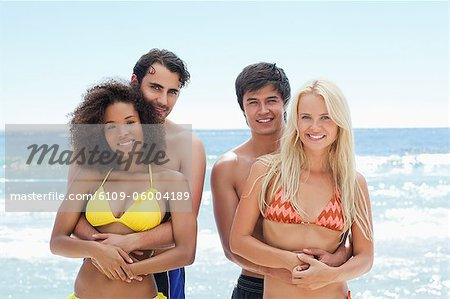 Two men holding their partners as they stand by the water in swimwear Stock Photo - Premium Royalty-Free, Image code: 6109-06004189