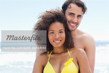 Man in swimwear happily smiling as he holds his friend by the water Stock Photo - Premium Royalty-Free, Image code: 6109-06004192