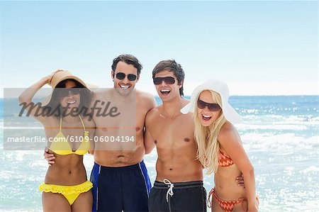 Two men and two women wearing swimwear as they hold each other by the water Stock Photo - Premium Royalty-Free, Image code: 6109-06004194