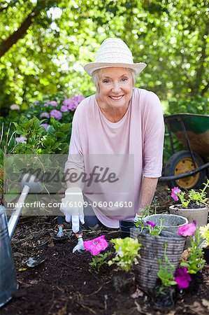 Woman smiling happily while planting pink flowers in her garden Stock Photo - Premium Royalty-Free, Image code: 6109-06004610