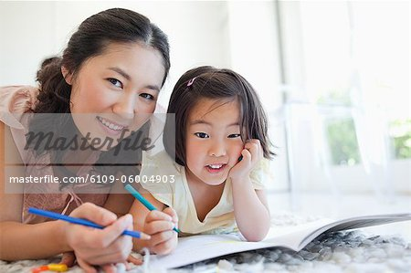 A mother and daughter smiling and looking ahead as they stop colouring for a moment. Stock Photo - Premium Royalty-Free, Image code: 6109-06004903