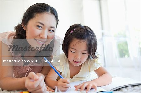 A mother looks up and smiles while her daughter continues to colour Stock Photo - Premium Royalty-Free, Image code: 6109-06004904
