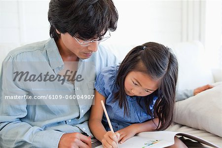 A father helps his daughter do her homework. Stock Photo - Premium Royalty-Free, Image code: 6109-06004907