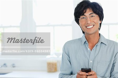 A smiling man uses his phone to send a text while looking straight ahead Stock Photo - Premium Royalty-Free, Image code: 6109-06004983