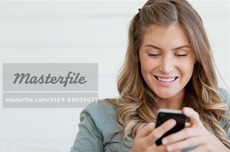 A smiling woman who is sitting while she uses her phone to send a text message Stock Photo - Premium Royalty-Free, Image code: 6109-06005031