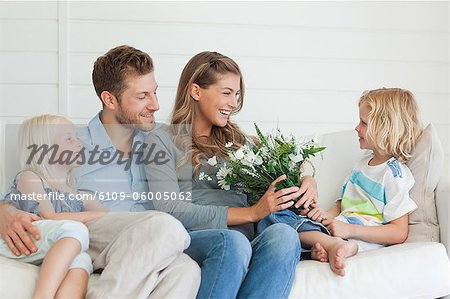 A son hands her mother a bouquet of flowers as the family sits on the couch Stock Photo - Premium Royalty-Free, Image code: 6109-06005062