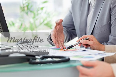 Close-up of people working on figures in an office Stock Photo - Premium Royalty-Free, Image code: 6109-06005258