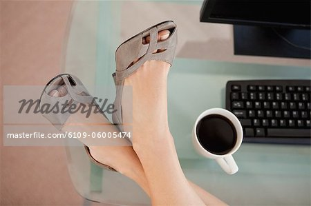 High angle-shot on businesswoman feet on a glass desk next to a coffee Stock Photo - Premium Royalty-Free, Image code: 6109-06005474