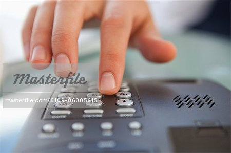 Close-up of a man dialing a telephone number on a landline phone Stock Photo - Premium Royalty-Free, Image code: 6109-06005615