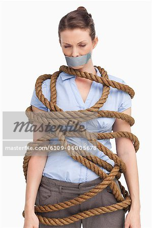 Businesswoman tied up against a white background Stock Photo - Premium Royalty-Free, Image code: 6109-06005678