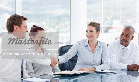 Young businesspeople shaking hands while sitting at a table Stock Photo - Premium Royalty-Free, Image code: 6109-06005845
