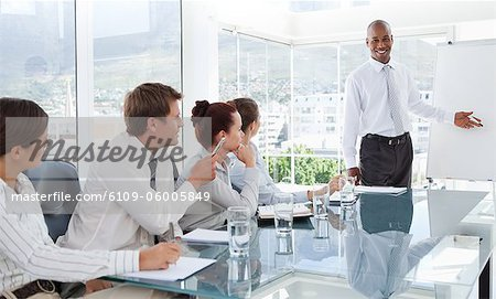 Smiling young businessman giving a presentation for his colleagues Stock Photo - Premium Royalty-Free, Image code: 6109-06005849