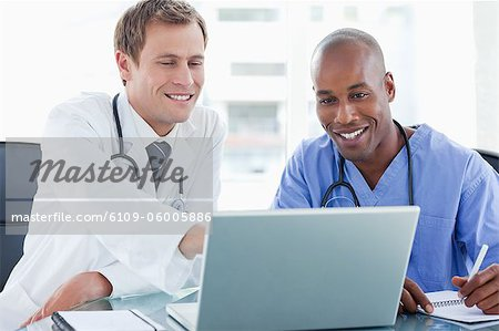 Smiling doctors working together with laptop Stock Photo - Premium Royalty-Free, Image code: 6109-06005886