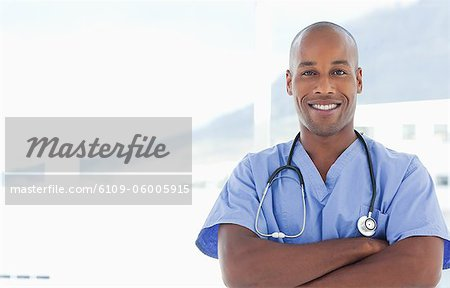 Smiling doctor with his arms crossed Stock Photo - Premium Royalty-Free, Image code: 6109-06005915