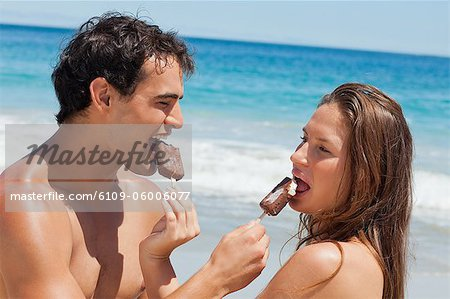 Close-up of lovers eating Popsicle together with sea in background Stock Photo - Premium Royalty-Free, Image code: 6109-06006077